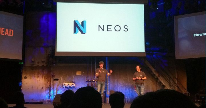 Photo taken of the two hosts presenting the new Neos CMS logo on stage during the 2016 Inspiring Conference.