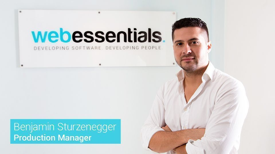 Web Essentials' Project Manager Benjamin Sturzenegger in front of the Web Essentials logo.