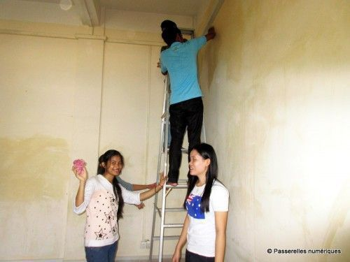 PNC students stand on a ladder making preparations to paint a wall.