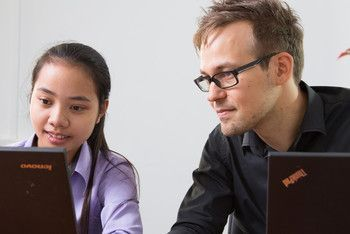 A European web technical lead assisting a Cambodian IT student.