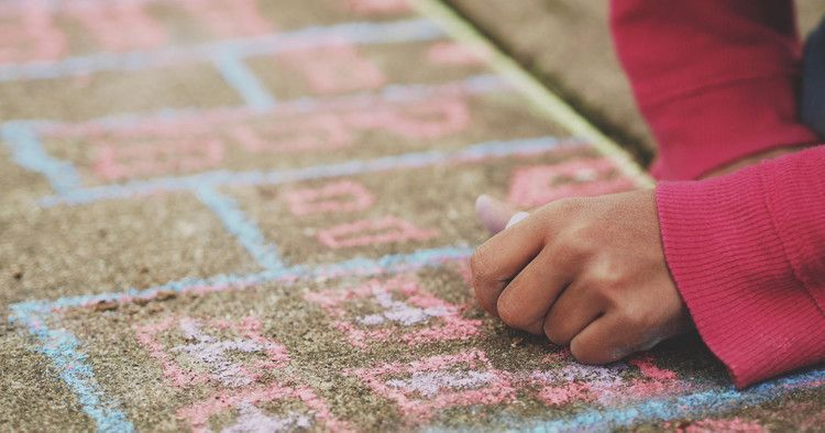A child is holding chalk and drawing on the street