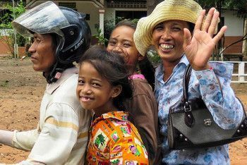 A Cambodian family of four riding one motorcycle, smiling and waving.