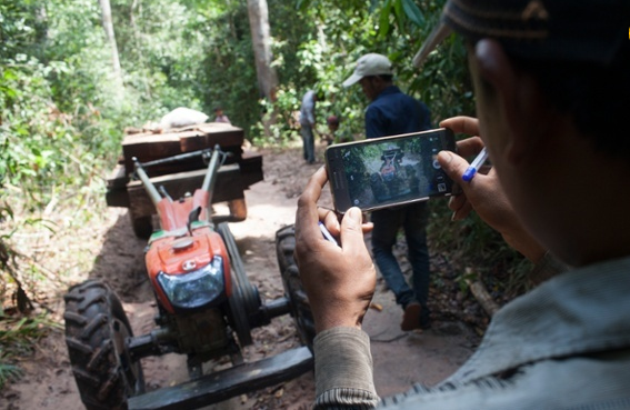 A man is taking a photo with his mobile phone of a small tractor hauling illegal timber in the Prey Lang forest.