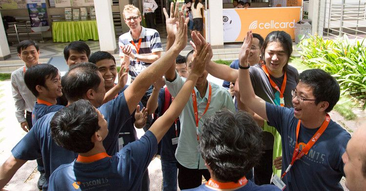 A group of developers from diverse backgrounds high fiving each other.