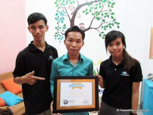 Three Web Essentials team members proudly holding a certificate of their donation to PNC students.